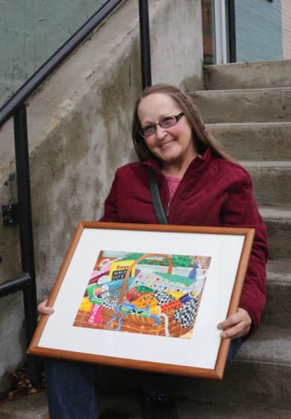 Sherridan holding her original painting; Photo credit: Jenny Rebecca Photography