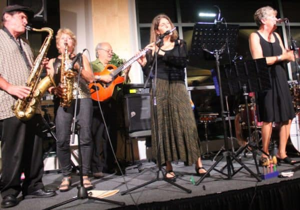 Multiple instrumentalists and a vocalist performing jazz music on stage